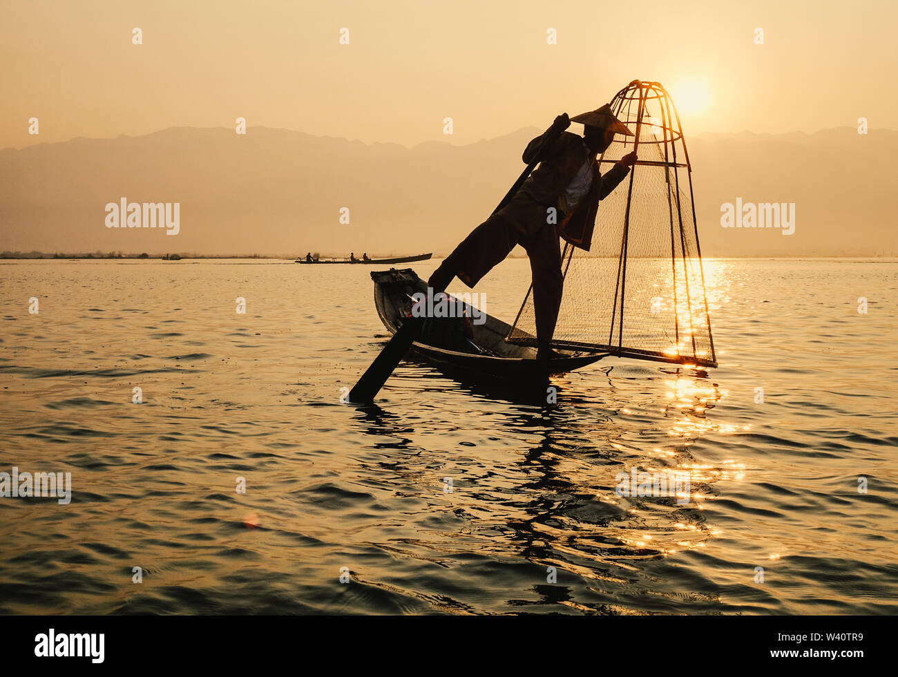Inle Lake, Myanmar - Feb 16, 2016. Intha man using the unique methods of rowing and catching fish on Inle Lake (Shan State). - Stock Image