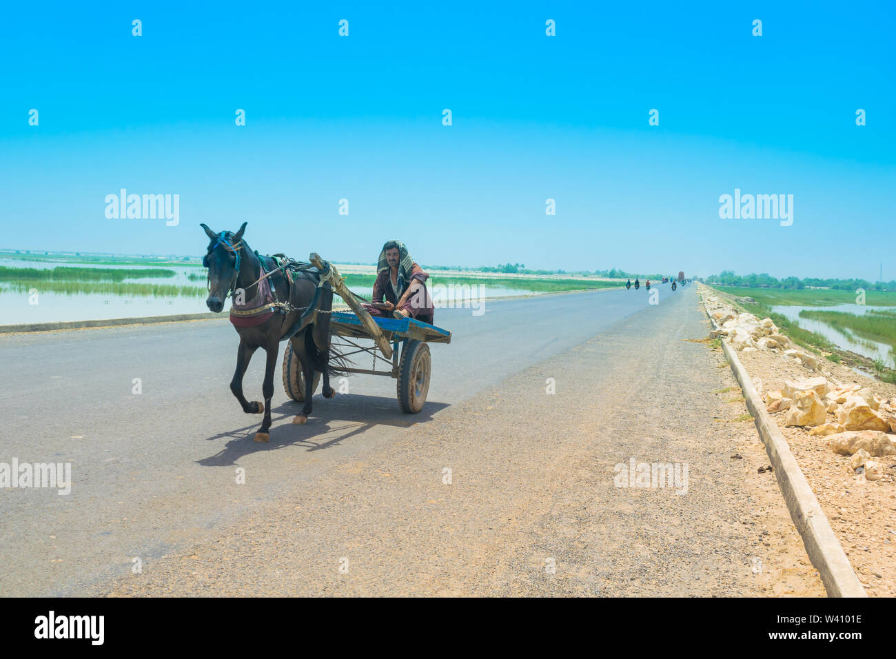 Rahim yar khan, Punjab,Pakistan-June 23,2019: a villager sitting on a horse cart on a high way,a man is driving a horse cart. Stock Photo