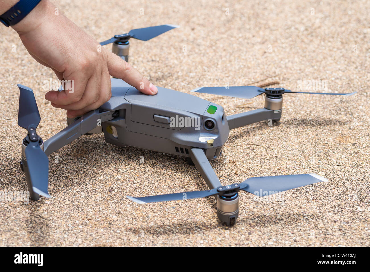 Male finger presses the launch button of the drone for flight, with which you can take photos and video filming, close-up - Stock Image