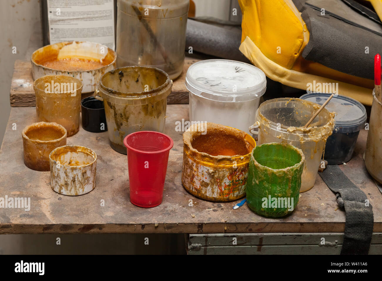 Multi-colored cans and containers with old dried paint and glue of yellow color on the table in the workshop for work with textiles and fabrics. Indus - Stock Image