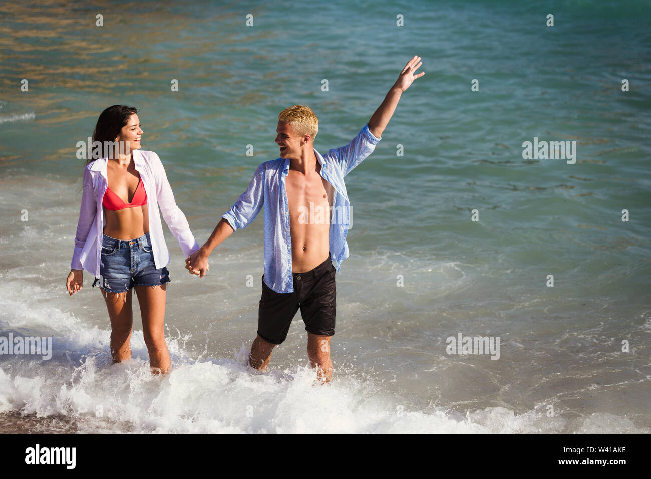 Happy young couple having fun and love at beach on sunny day - Stock Image