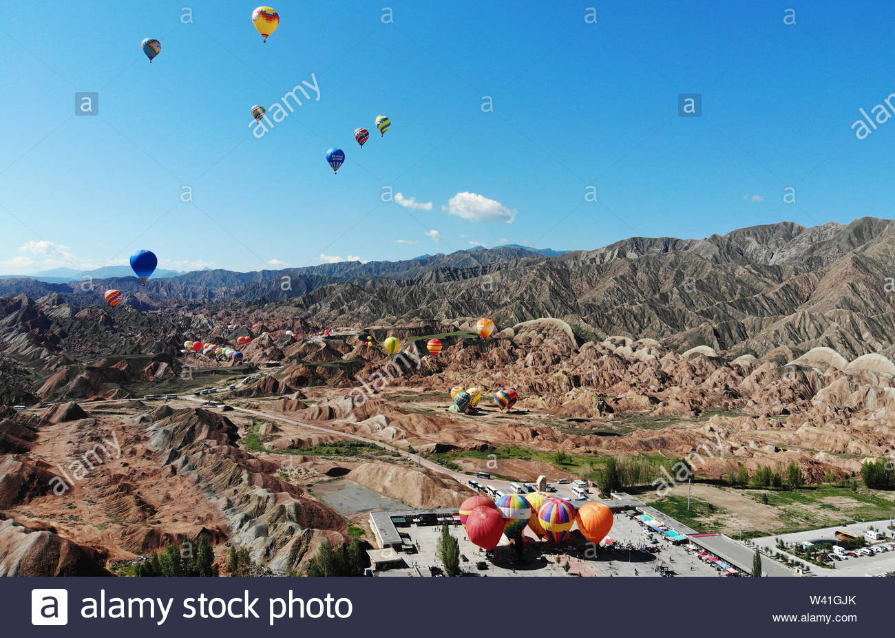 Zhangye, China. 18th July, 2019. One hundred athletes cross the colorful danxia scenic area by hot-air balloons in Zhangye, Gansu, China on 18th July, 2019.(Photo by TPG/cnsphotos) Credit: TopPhoto/Alamy Live News - Stock Image