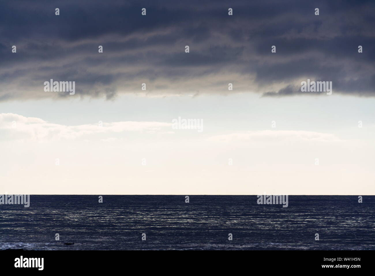 Large copy space for text on sky stripe between sea and clouds, sunrise on summer day - Stock Image