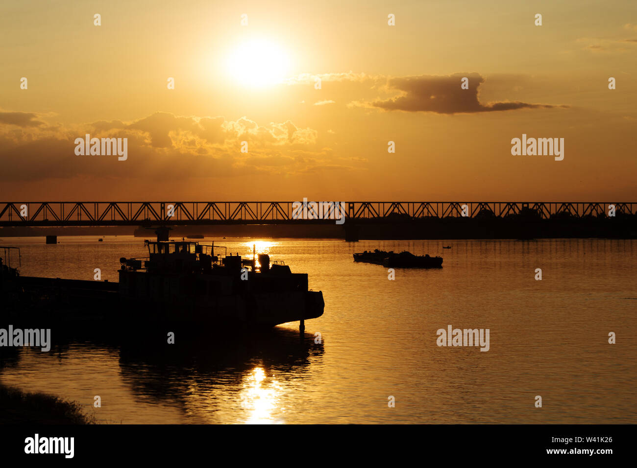 Beautiful Golden Sunset with Ships and Bridge Silhouettes At The River Danube in Belgrade Serbia - Stock Image