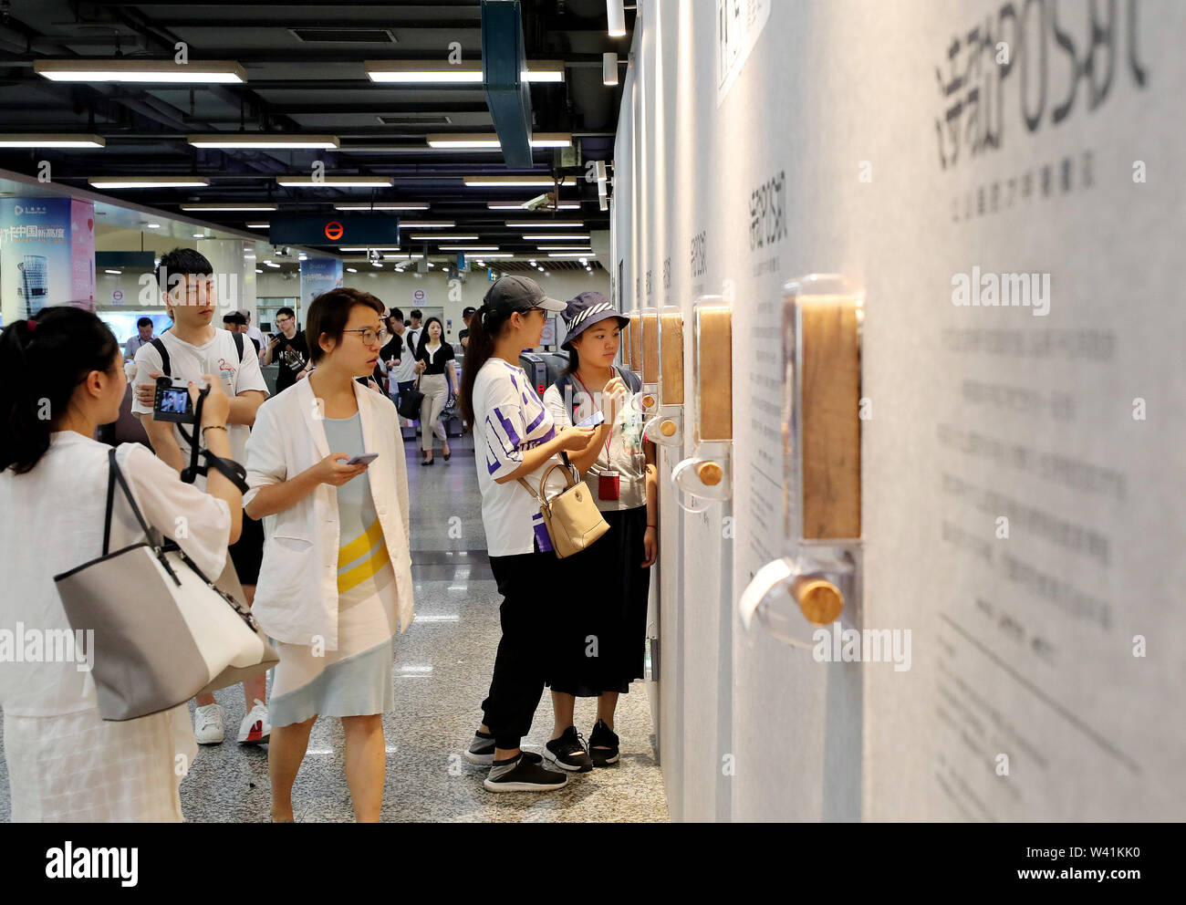 Shanghai. 19th July, 2019. Passengers view point-of-sale (POS) terminals on a wall at Lujiazui subway station in east China's Shanghai, July 19, 2019. A total of 15 POS terminals recently appeared at Lujiazui Station of subway Line 2 in Shanghai. By linking their cellphones to the terminals, passengers can donate one yuan (about 15 U.S. cents) to get a poem written by children in remote rural areas printed on a receipt. All raised money will be used for charity to promote education in these areas. Credit: Fang Zhe/Xinhua/Alamy Live News - Stock Image