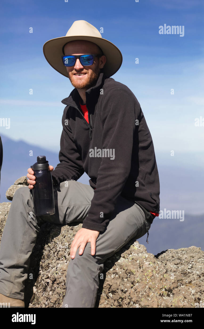 Smiling guy with white teeth, sunglasses on the face, hat. Wearing comfortable sportswear to climb the powerful mountain. Strong and shapely body. Stock Photo