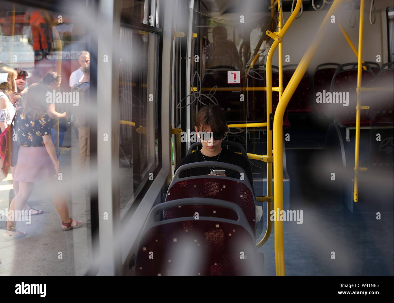 Yekaterinburg, Russia. 19th July, 2019. YEKATERINBURG, RUSSIA - JULY 19, 2019: A girl in a Belkommunmash electric bus during a test run along Trolleybus Route 1, from Shchorsa Street to a railway station. The bus, manufactured by Belarus' Belkommunmash Company, was displayed at the 2019 Innoprom exhibition. Donat Sorokin/TASS Credit: ITAR-TASS News Agency/Alamy Live News - Stock Image