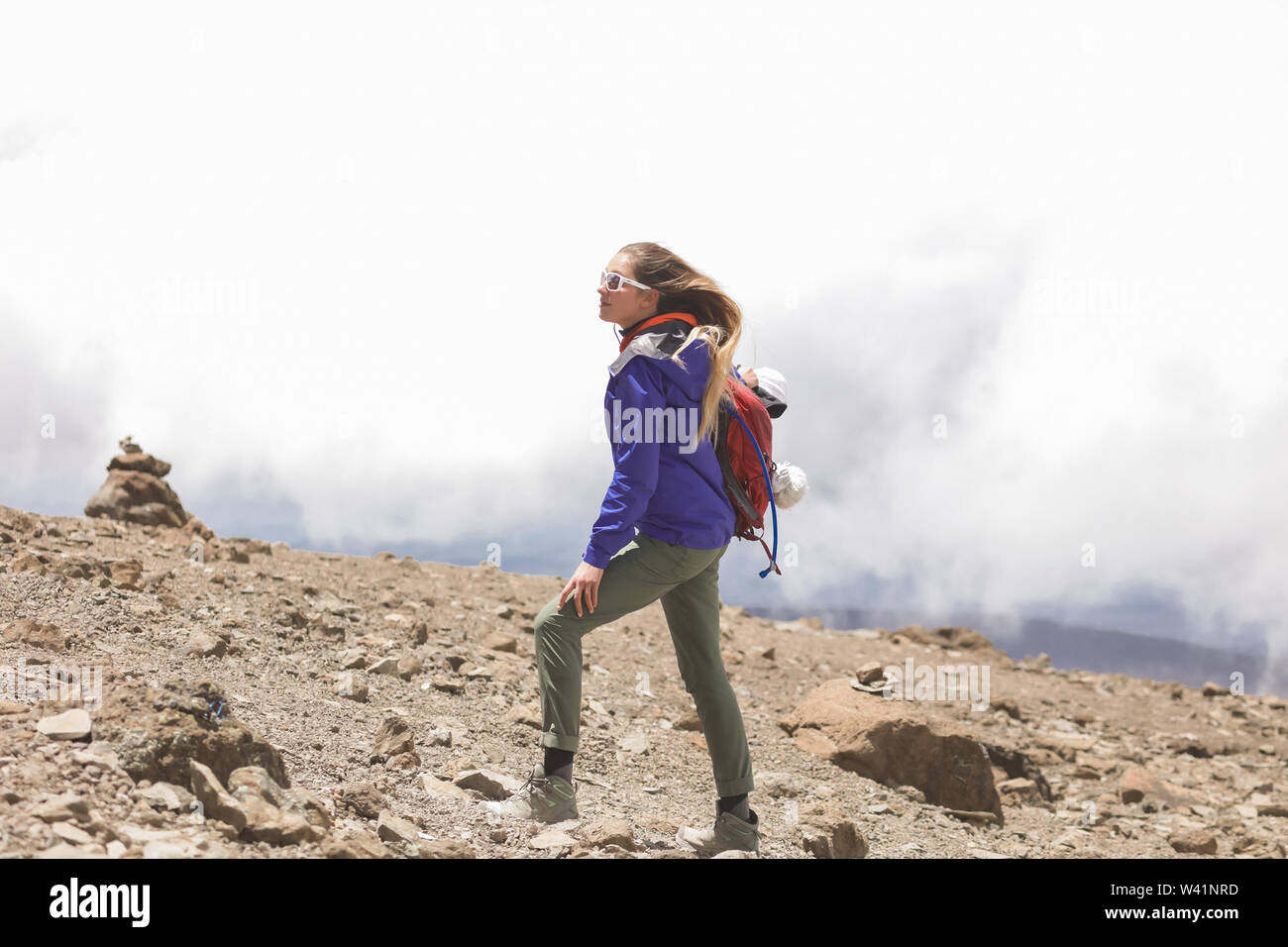 Shapely blonde having a rest between long distances and climbing to the mountain. High Kilimanjaro top with rocks and no plants. White clouds behind Stock Photo