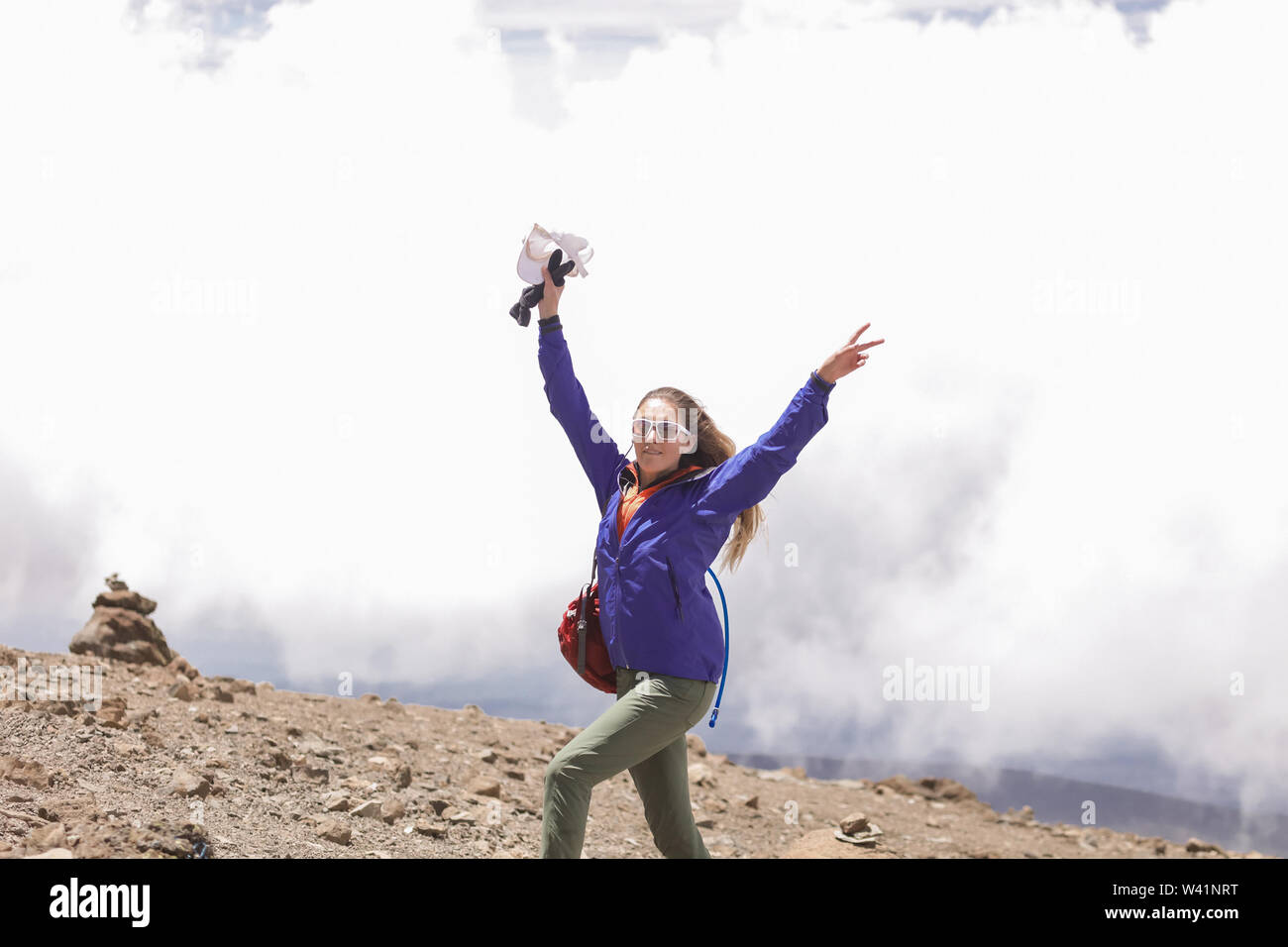 Energetic active girl posing for photo on the white clouds background. Standing on the top of the Kilimanjaro with raised hands. Holding a white cap, Stock Photo