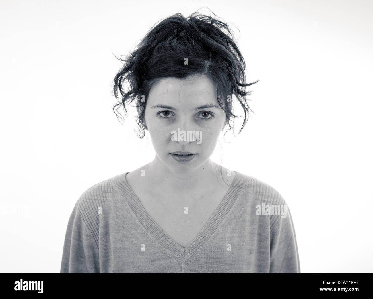 Close up of young attractive caucasian woman with an angry face. Looking mad and crazy shouting and making furious gestures. Isolated on neutral backg - Stock Image