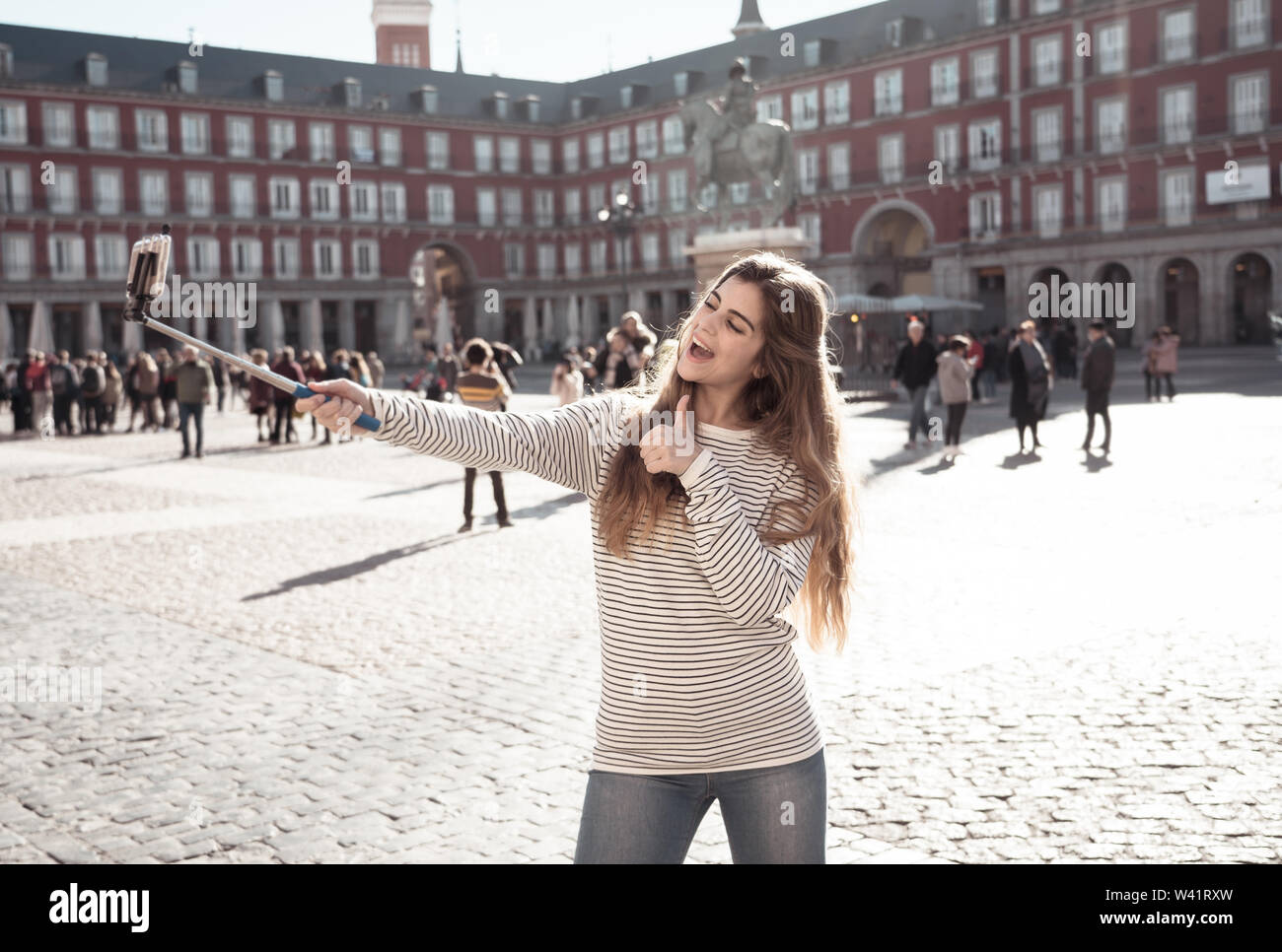 Beautiful and cheerful young woman happy and excited in Plaza Mayor Madrid taking selfie on smartphone making thumbs up gesture. In tourism student li - Stock Image