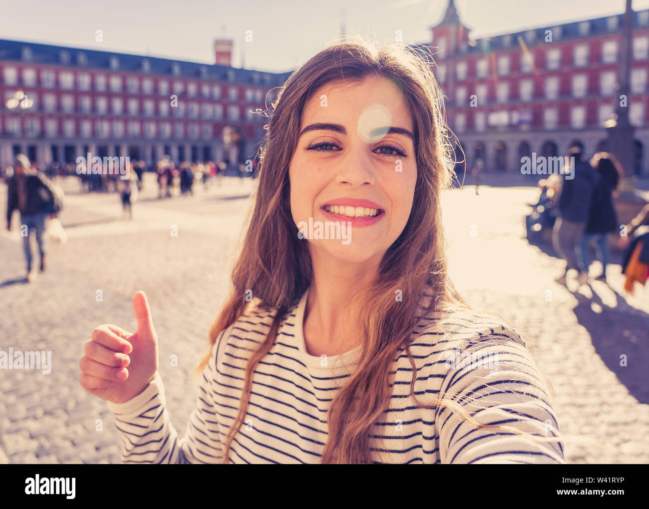 Beautiful young student tourist woman happy and excited in Plaza Mayor Madrid taking a selfie holding the mobile or tablet. Looking cheerful making th - Stock Image