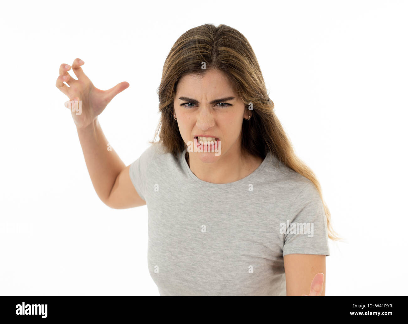 Close up of young attractive caucasian woman with an angry face. Looking mad and crazy shouting and making furious gestures. Isolated on white backgro - Stock Image
