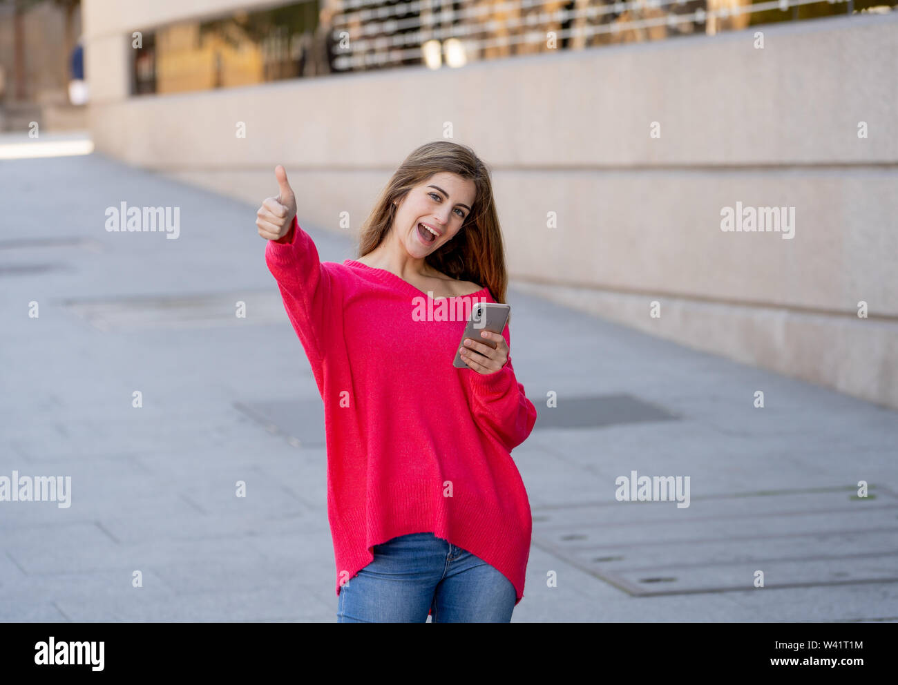 Young attractive happy woman using mobile smart phone making thumb up sign outside in city street. Beautiful teenager wearing stylish clothes feeling - Stock Image