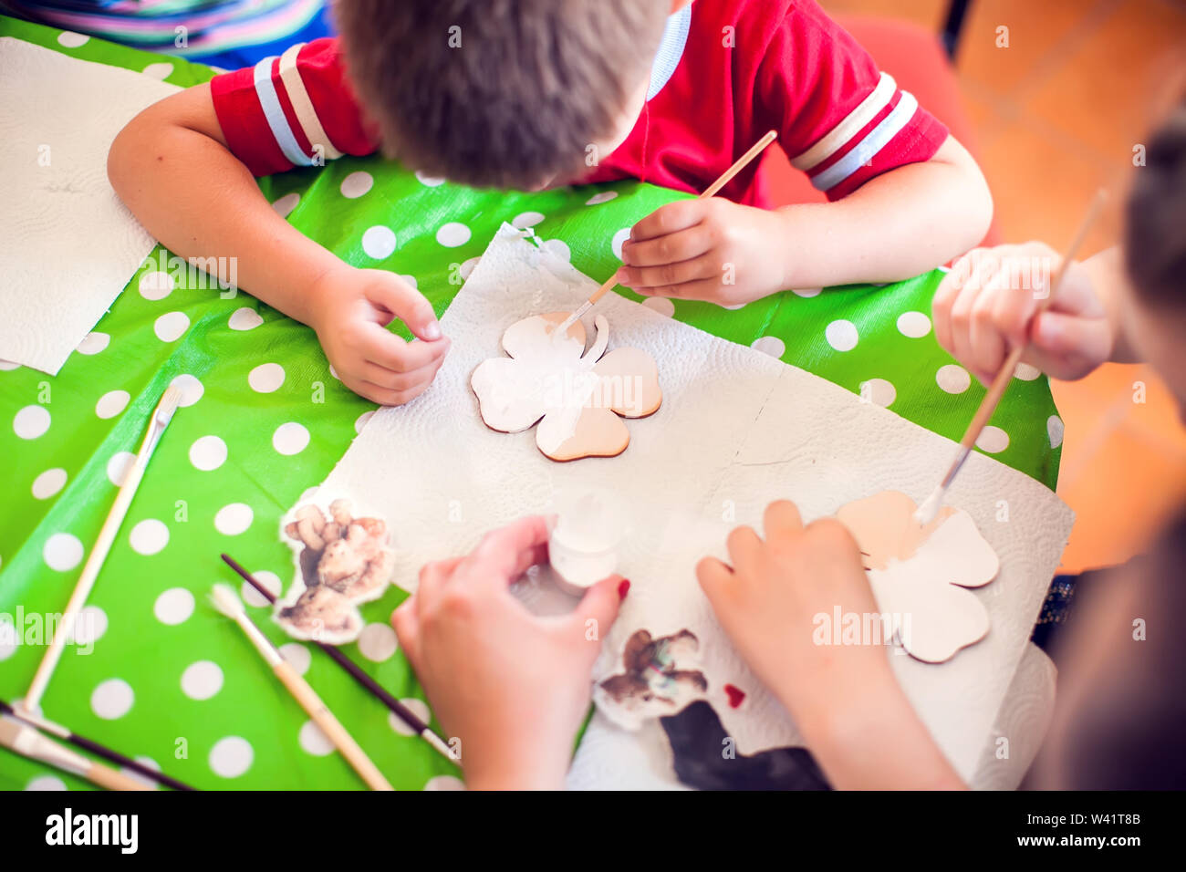 Children hands making artworks with wood and paint crafts. workplace and handcraft Decoupage Stock Photo