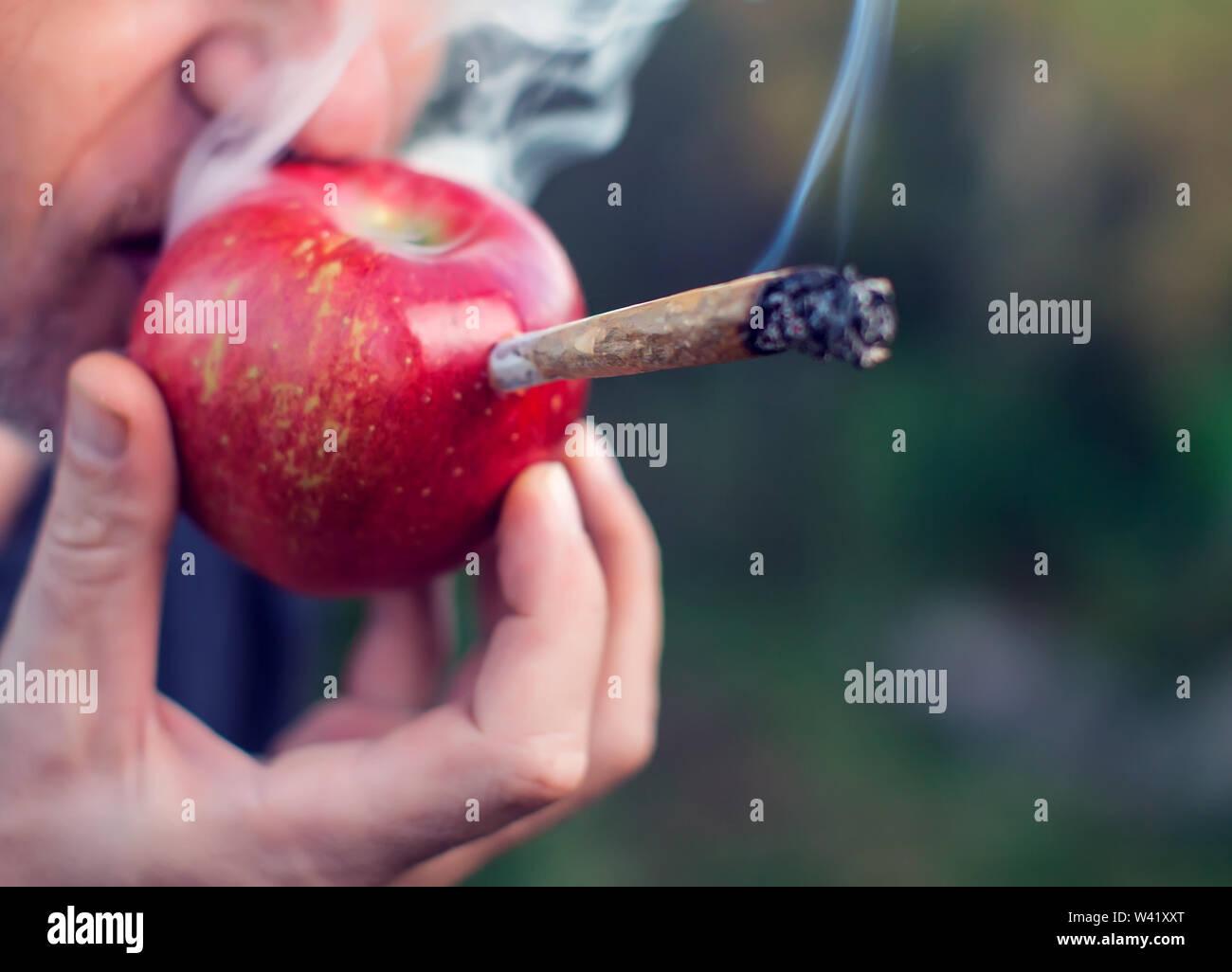 A man smoking marijuana joint through an apple. Light drugs concept Stock Photo - Alamy