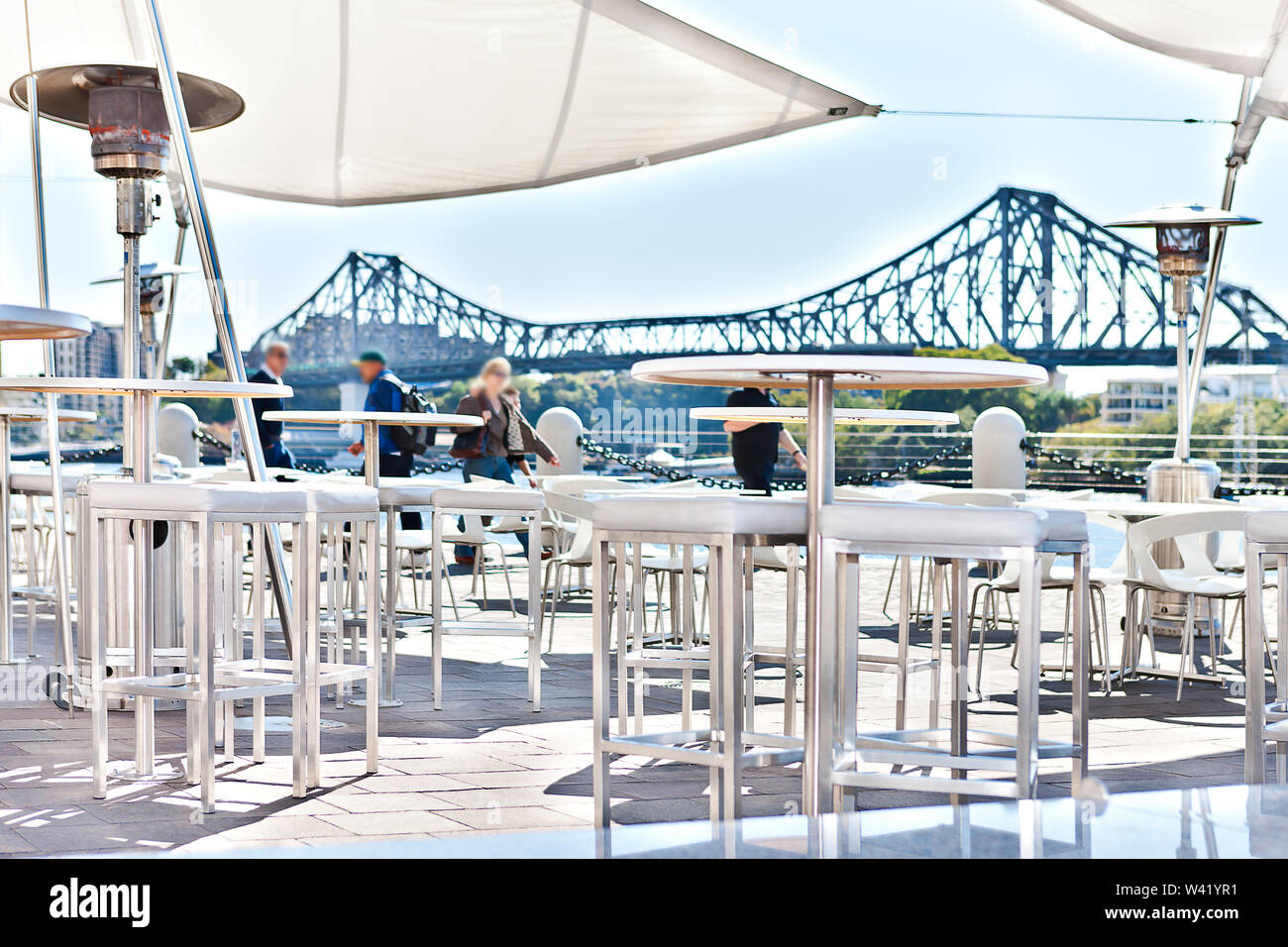 Outside patio or relaxation area with people, including white chairs and tables that covered with tent beside river in a sunny day of Brisbane City, Q - Stock Image