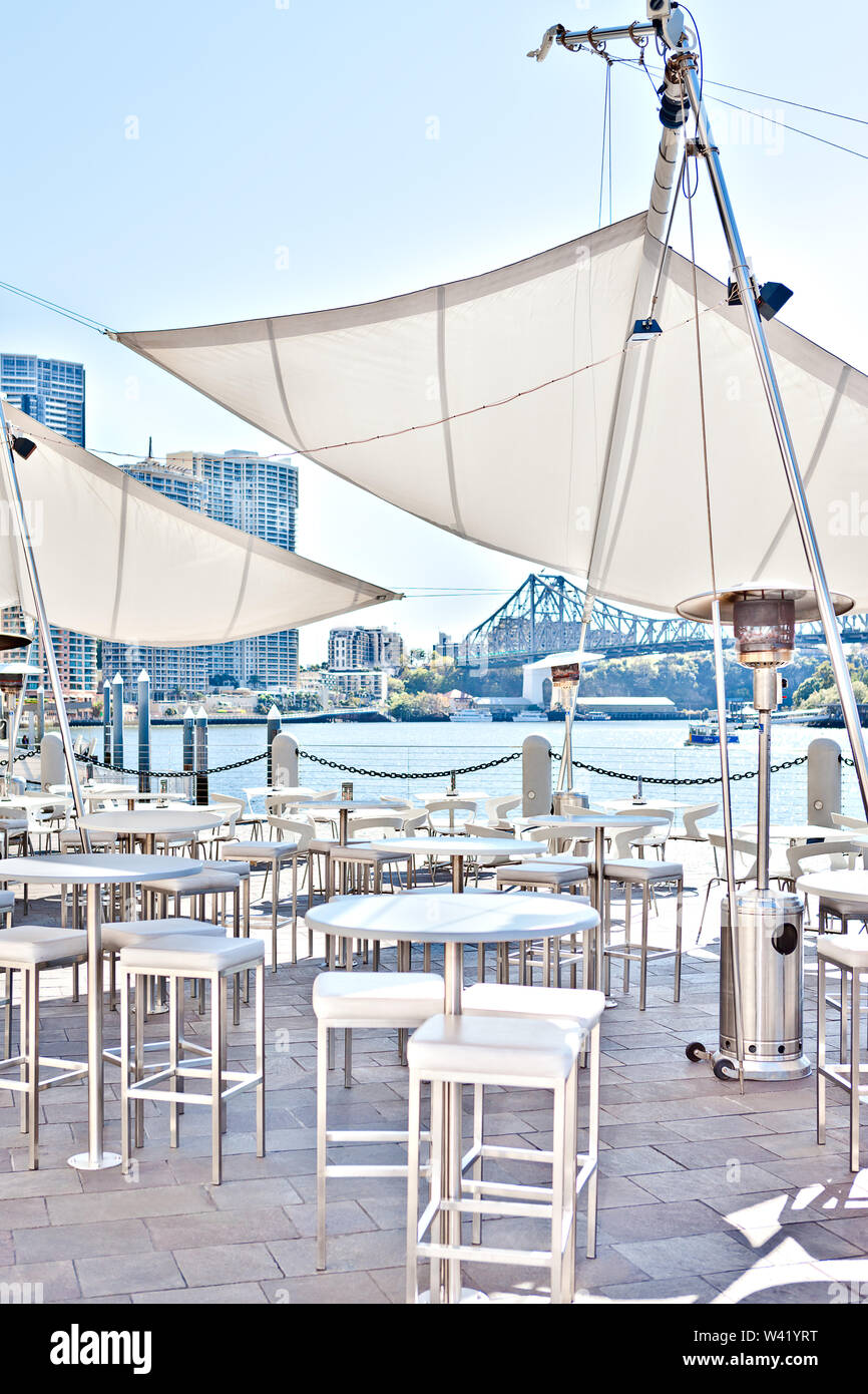 outside restaurant area near to the river and the fence with city and buildings from the background, including white chairs and tables that covered wi - Stock Image