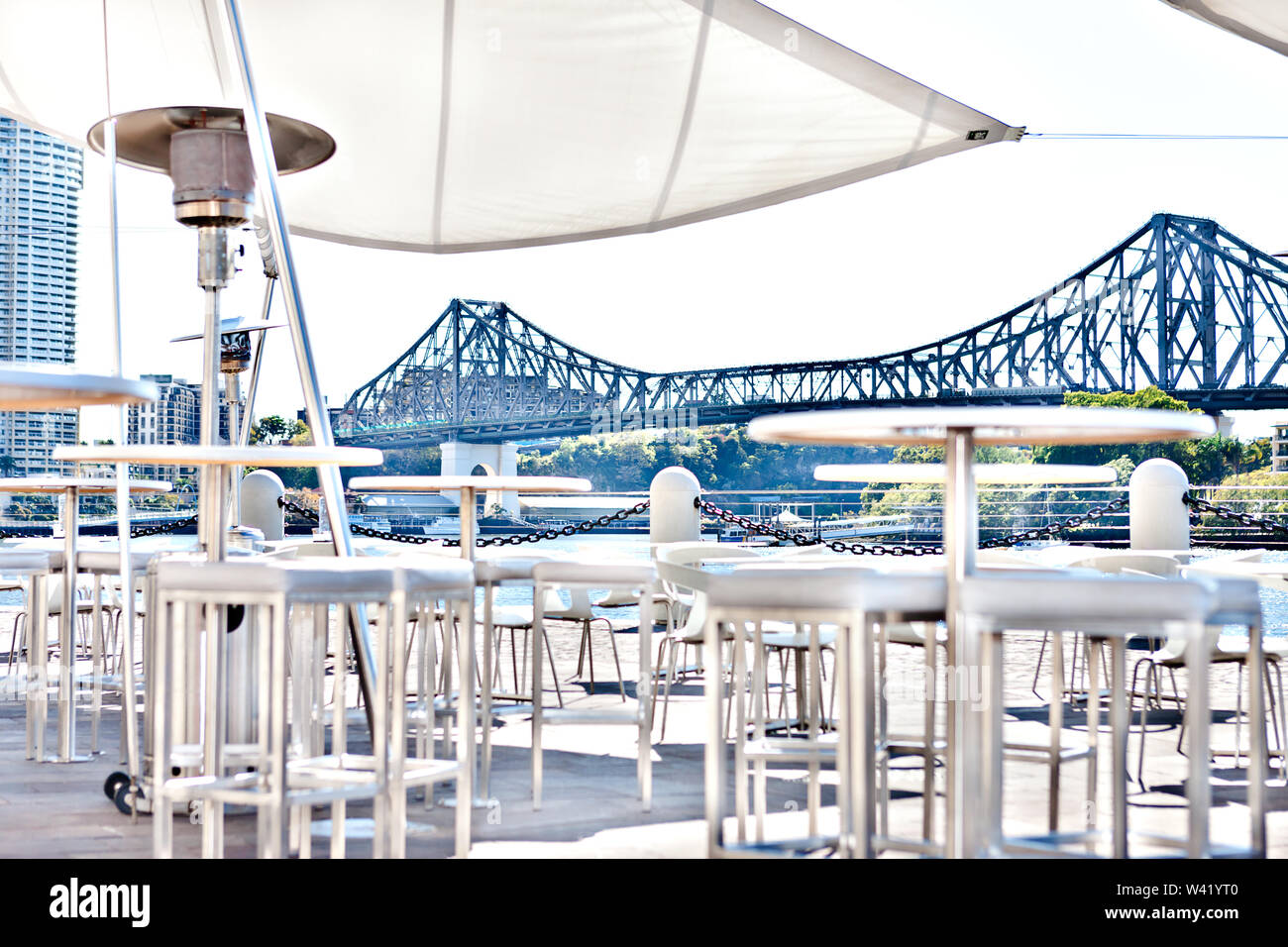 An outside relaxation area with a long bridge from the background, including white chairs and tables that covered with tent beside river in a sunny da - Stock Image