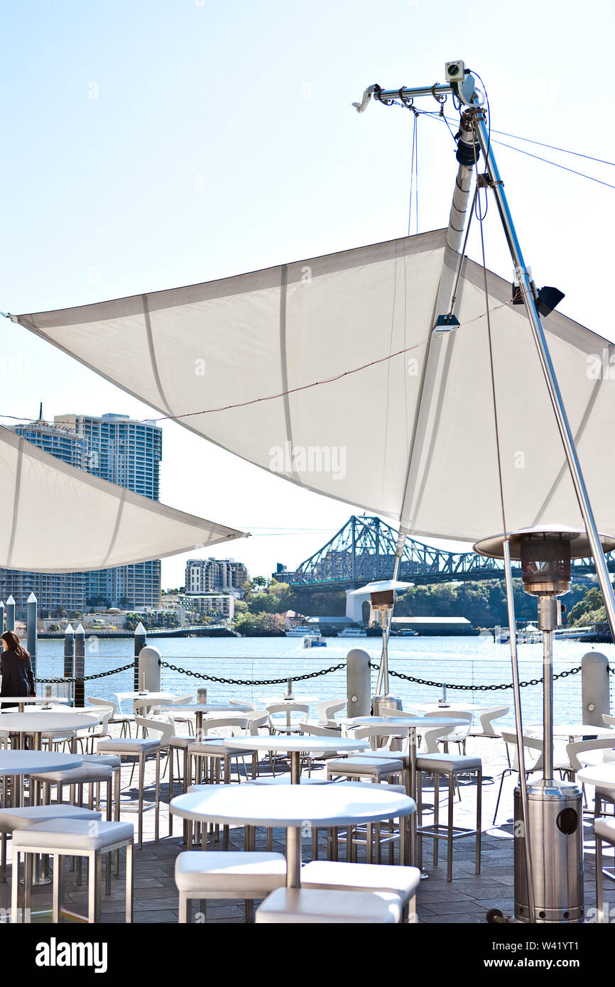 Modern riverside patio area with round and white tables with chairs of a city Brisbane City, Queensland, Australia. - Stock Image