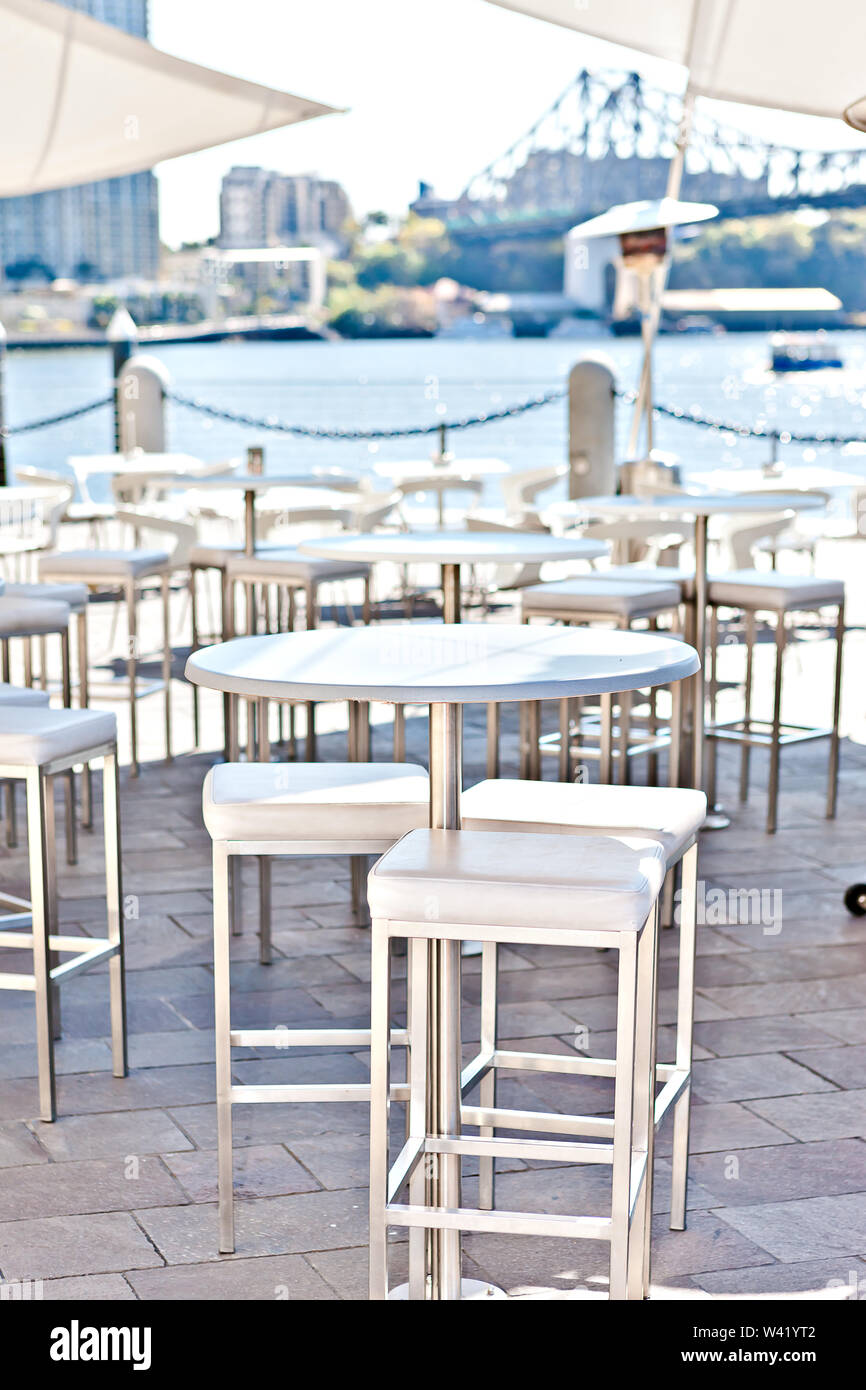 Close view of the round white  chairs and tables in outside dining or patio area next to the river water side from Brisbane City, Queensland, Australi - Stock Image