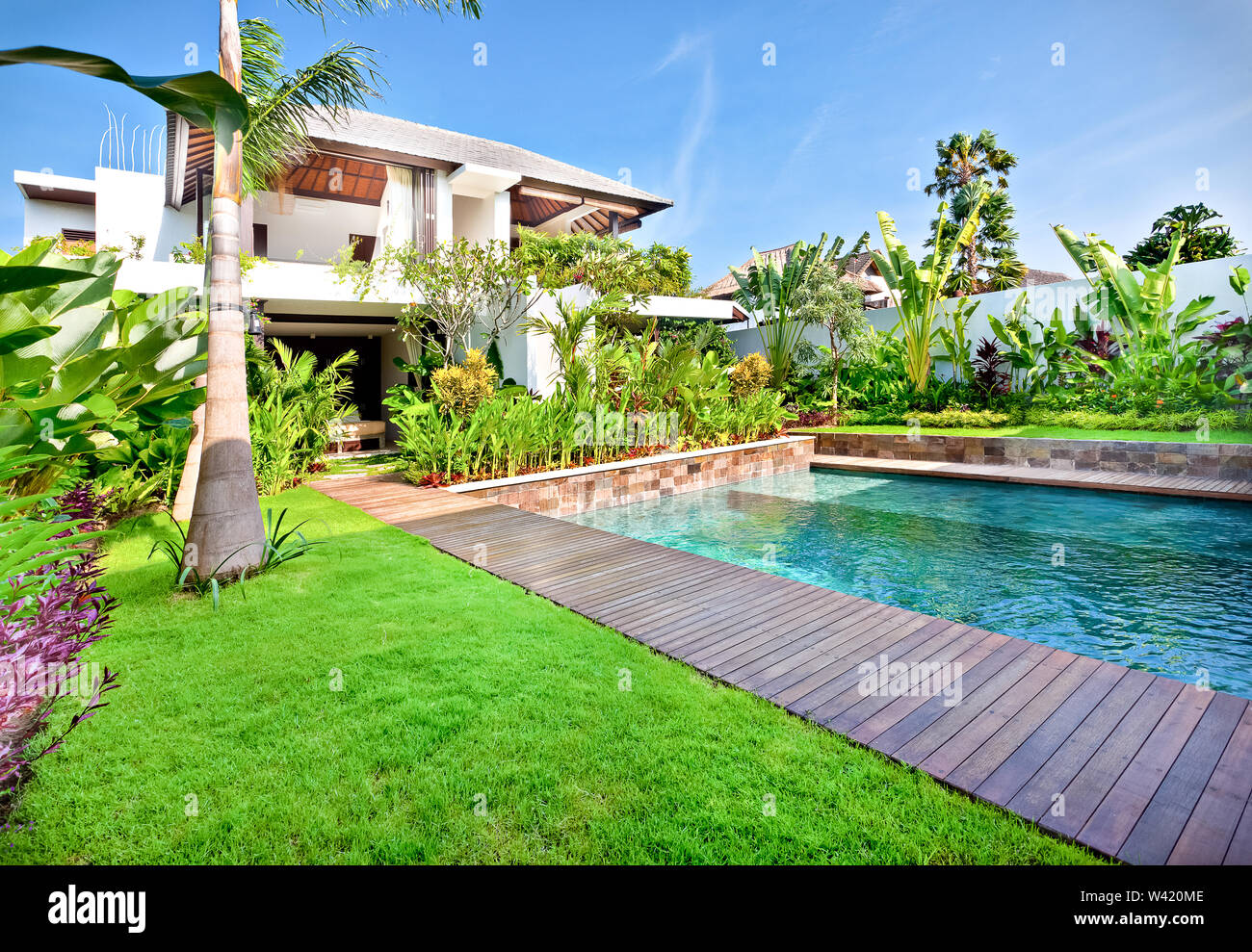 Green lawn with a garden including swimming pool in a modern house and blue sky - Stock Image