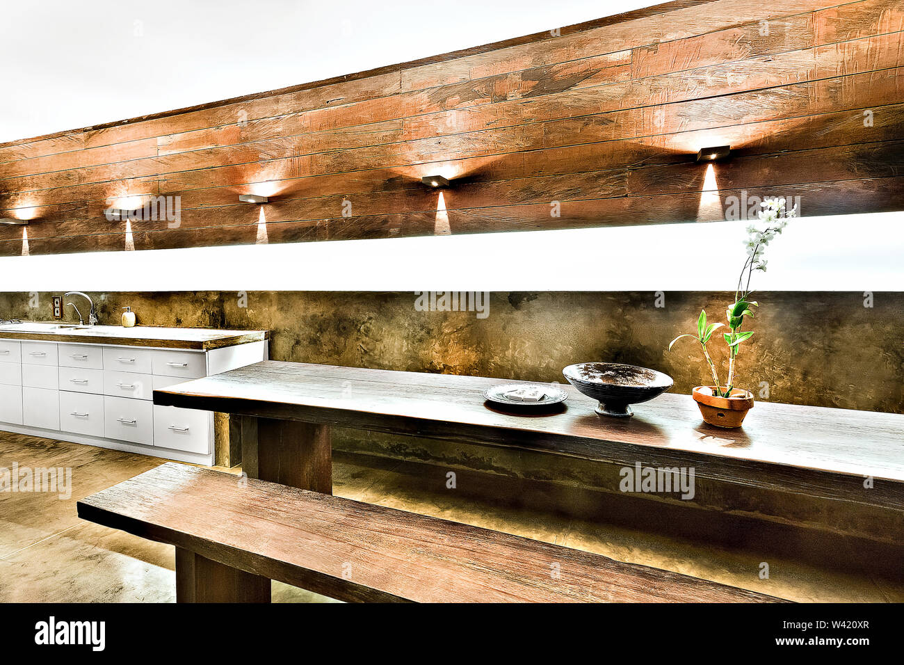 Outdoor dining or patio area with wooden furniture including benches and tables under the flashing lights Stock Photo