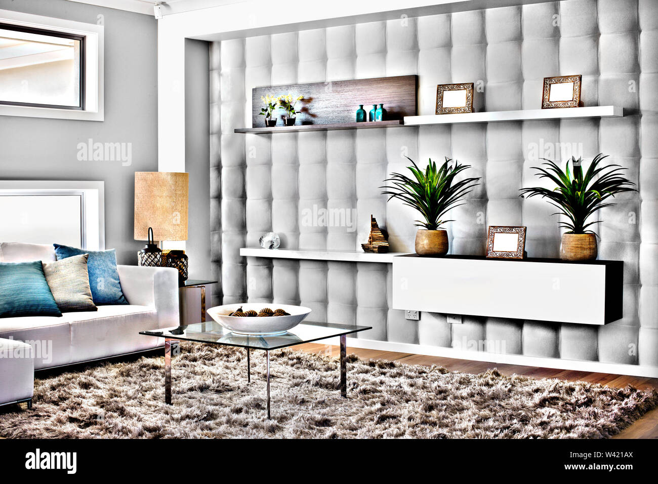 Modern Living Room With The Carpet And Glass Table Beside The Rack Full Fancy Items Like Plants In The Vase Near To The Lamp And Sofa With Pillows Stock Photo Alamy