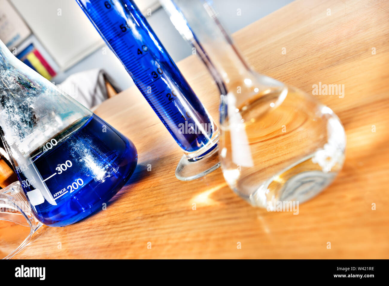 Science equipment in a laboratory, including beakers and tubes with blue liquid on a wooden table closeup Stock Photo