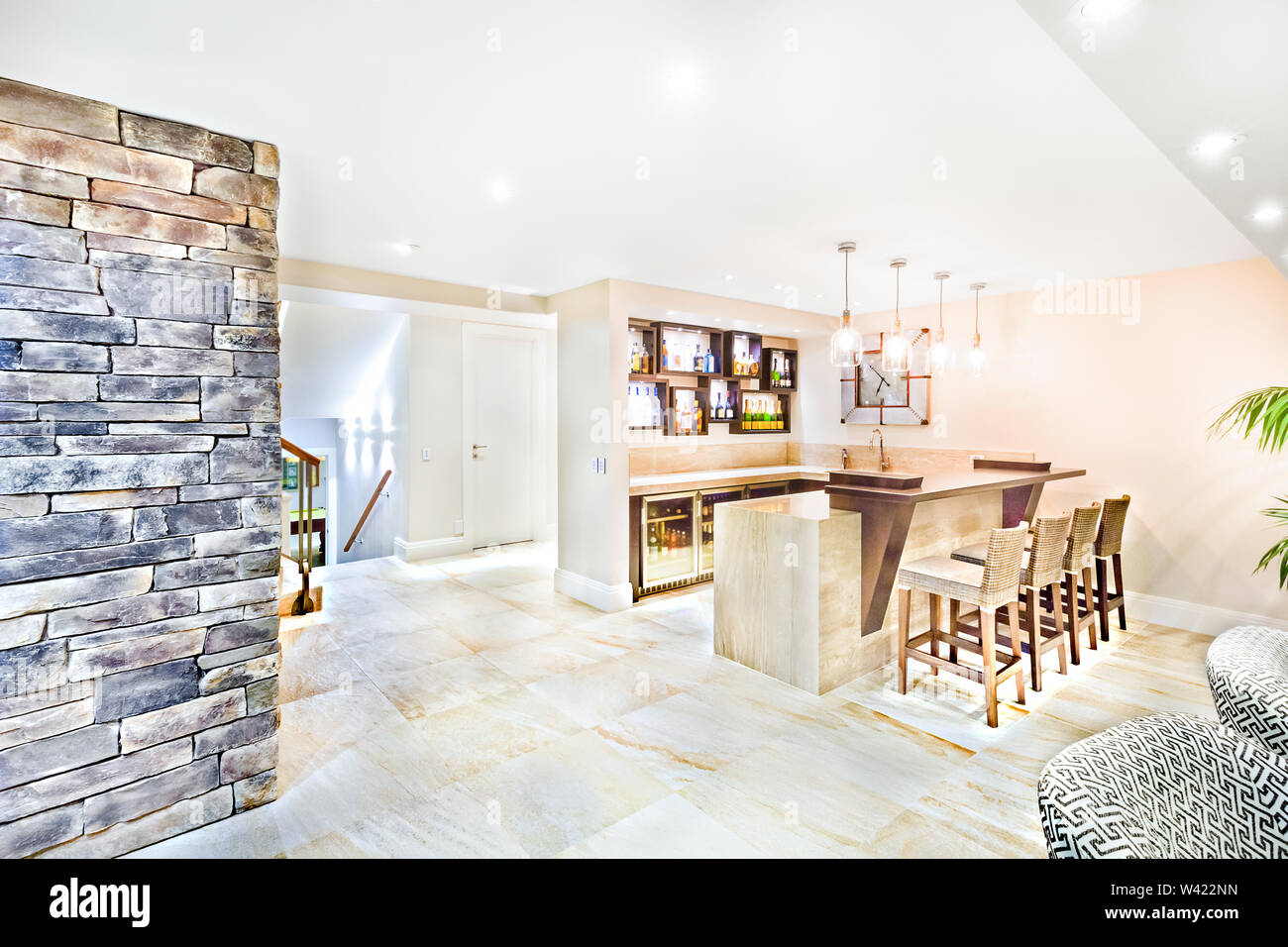 Living room including dining area with furniture, floor is tiled, sink can see on the table, vine bottles in wall cupboards, perfect lights balancing, Stock Photo