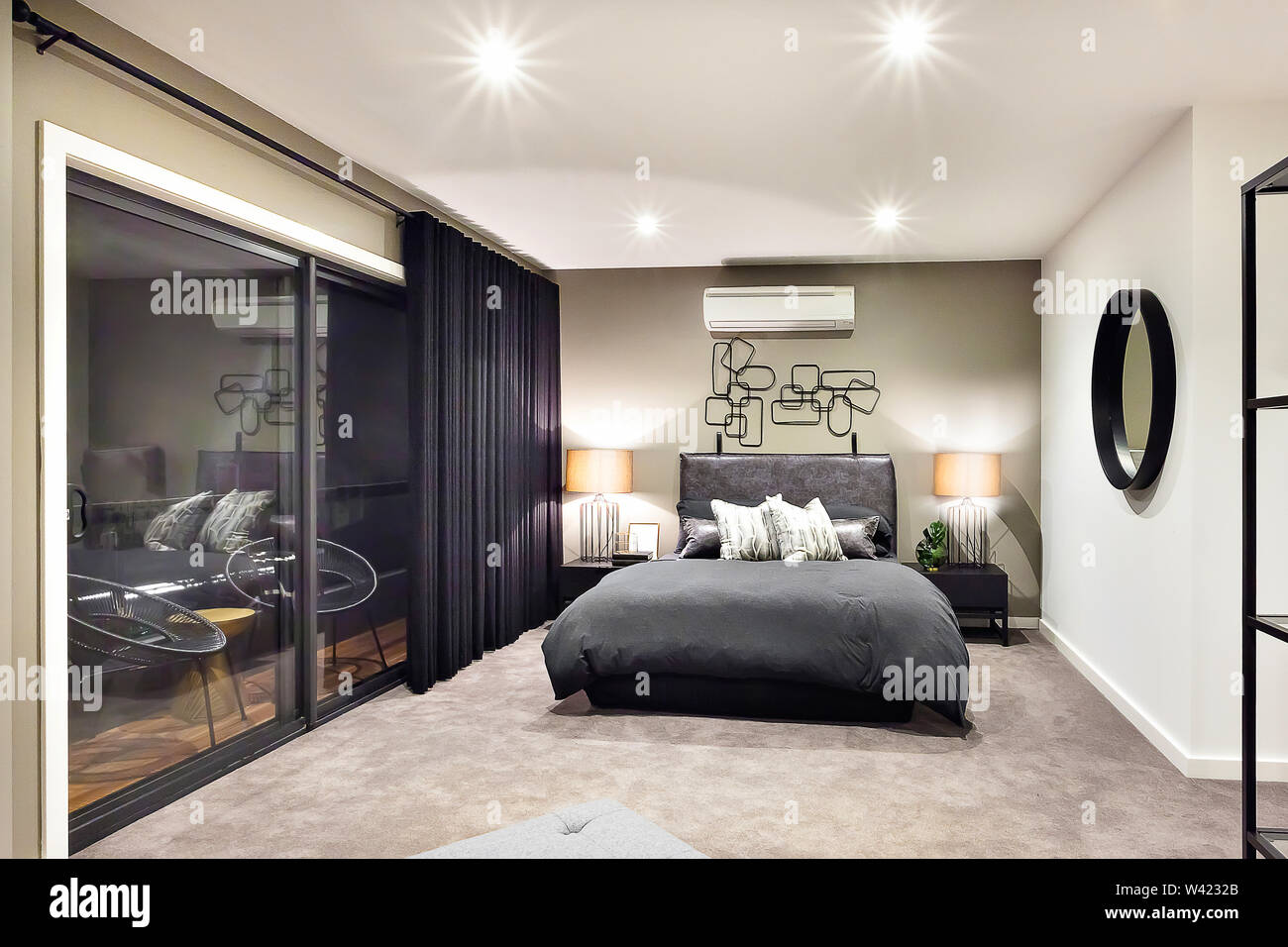 Black color bed in luxurious hotel or house  with flashing lamps beside a glass door or window Stock Photo