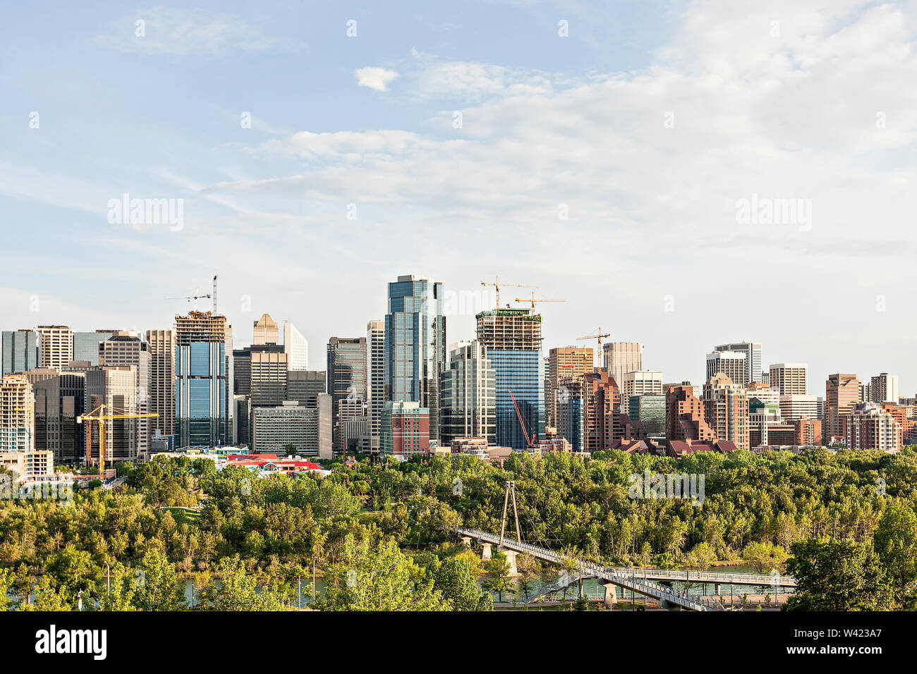 Luxury city with huge buildings and forest, sky has white clouds, long bridge can see near jungle, morning time or evening city view. - Stock Image