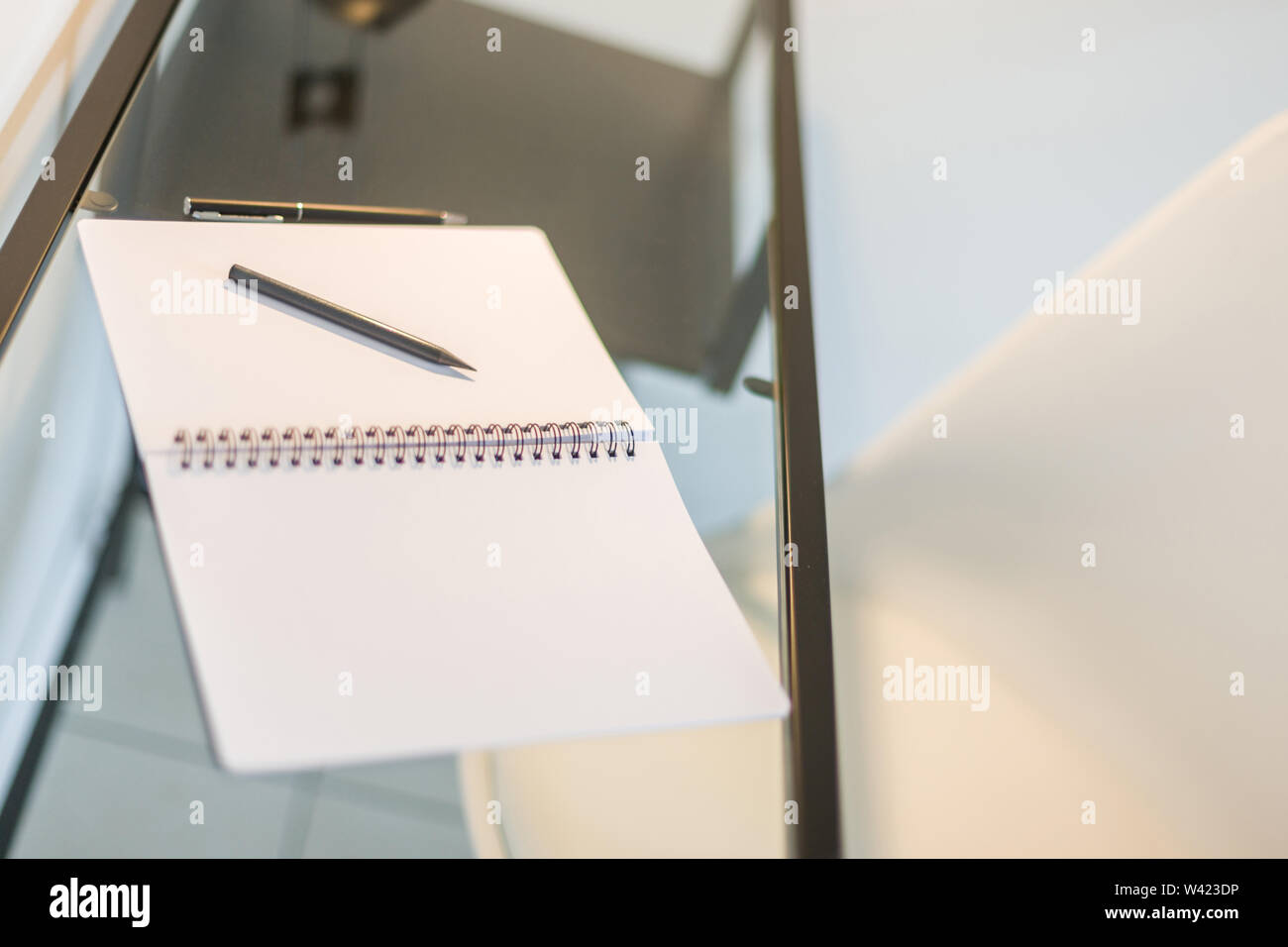 Tilted view of a notebook, pencil and a pen kept on a glass table with a wrought iron frame Stock Photo