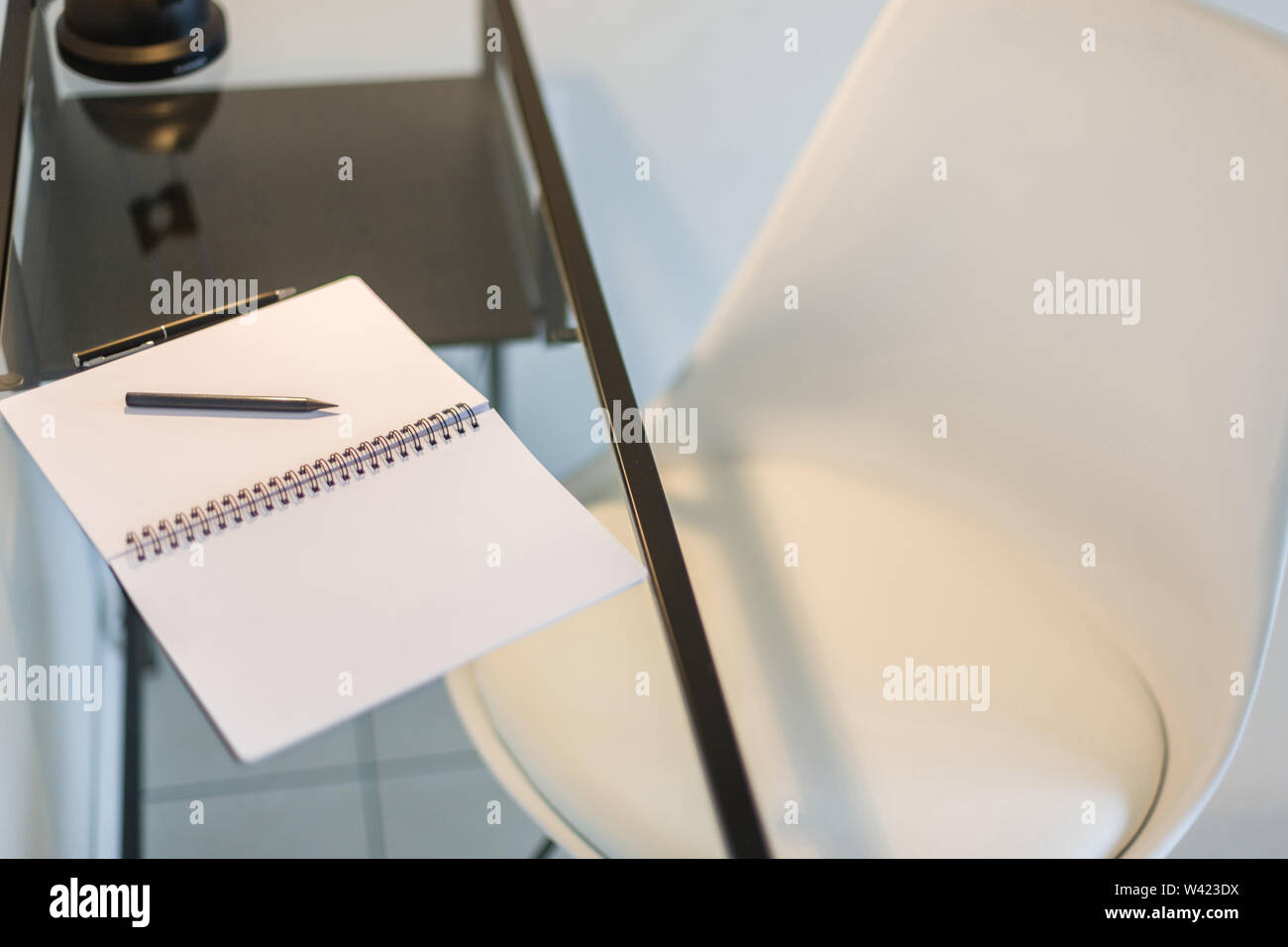 Top view of a stylish white chair and a glass study table with a notebook, pen and pencil kept on it Stock Photo