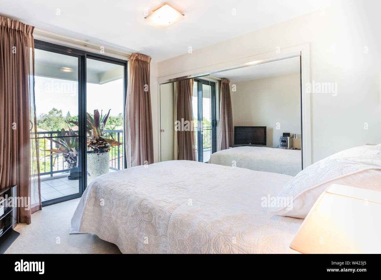 A Bedroom With A Comfortable Bed And A Large Mirror Along With A Large Balcony Area Outside Stock Photo Alamy