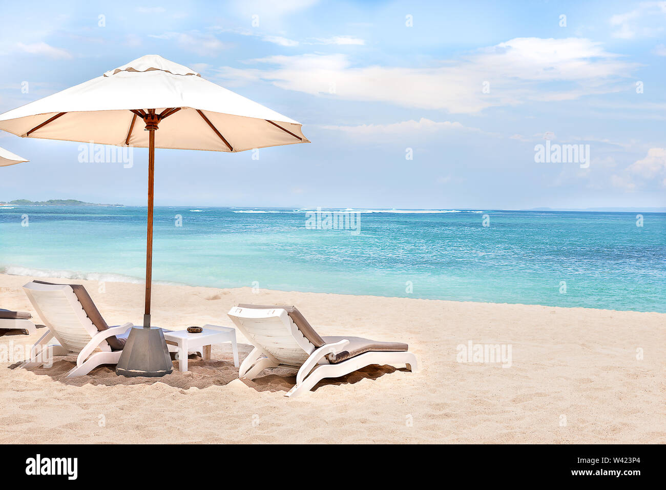 Beach side rest chairs and umbrellas on the sand near the blue water and horizon - Stock Image