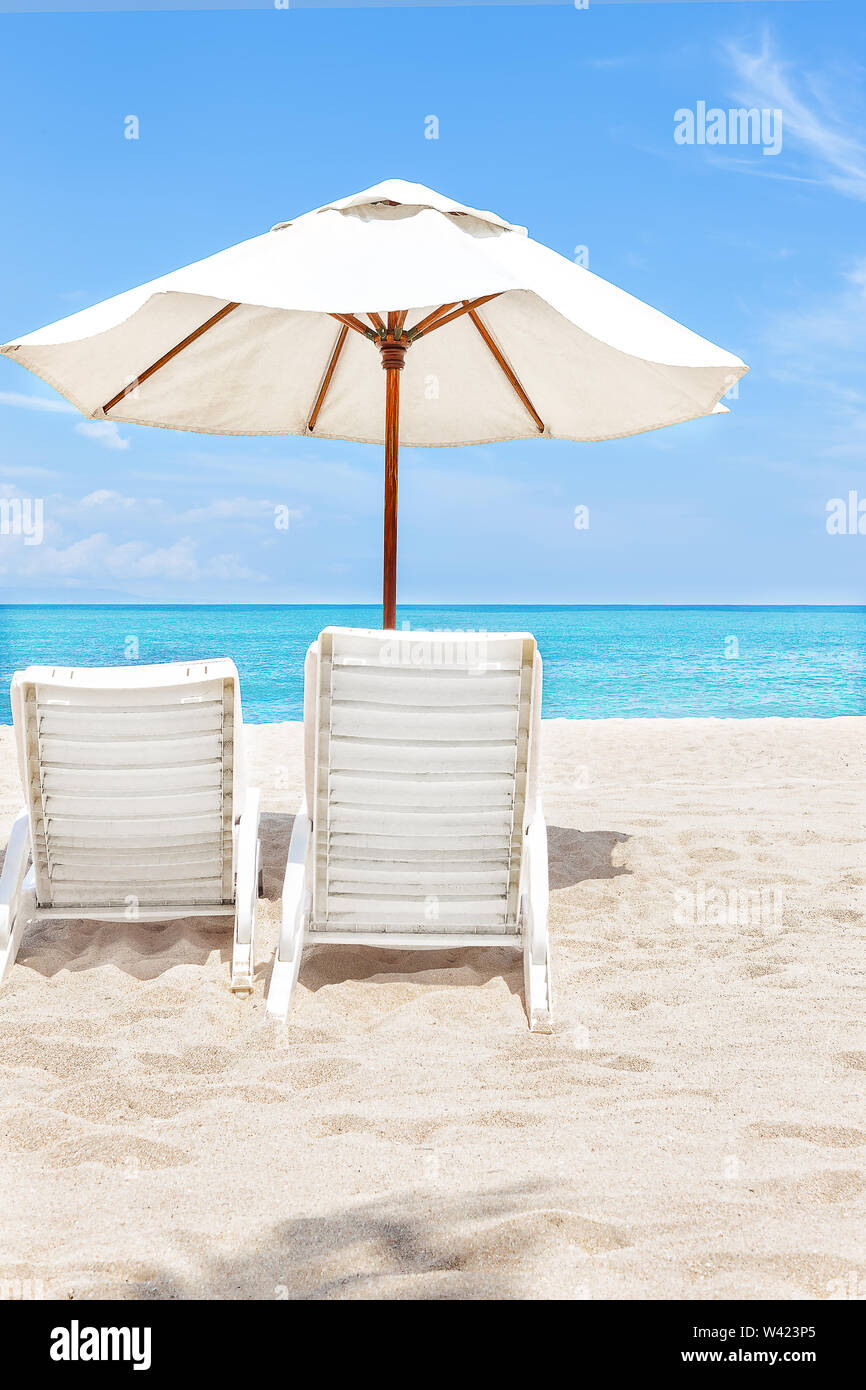 Back of the beach chairs and umbrellas on the sand near the ocean and horizon - Stock Image