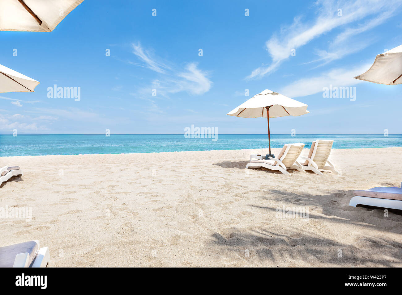 Ocean side chairs and umbrellas closeup  with blue sky and water giving the beauti of horizon - Stock Image