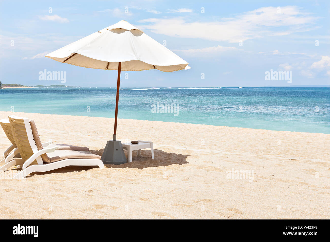 Closeup of the sun beds and umbrellas on the sand near the beach giving the look of the horizon - Stock Image