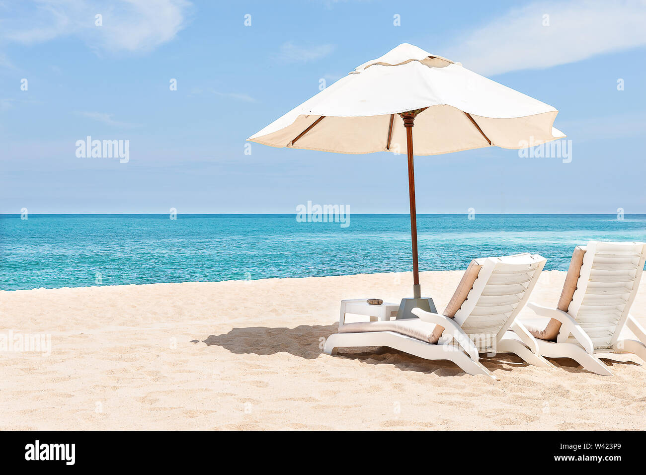 Sea chairs and umbrellas on the sand near blue water side with horizon and clear sky - Stock Image