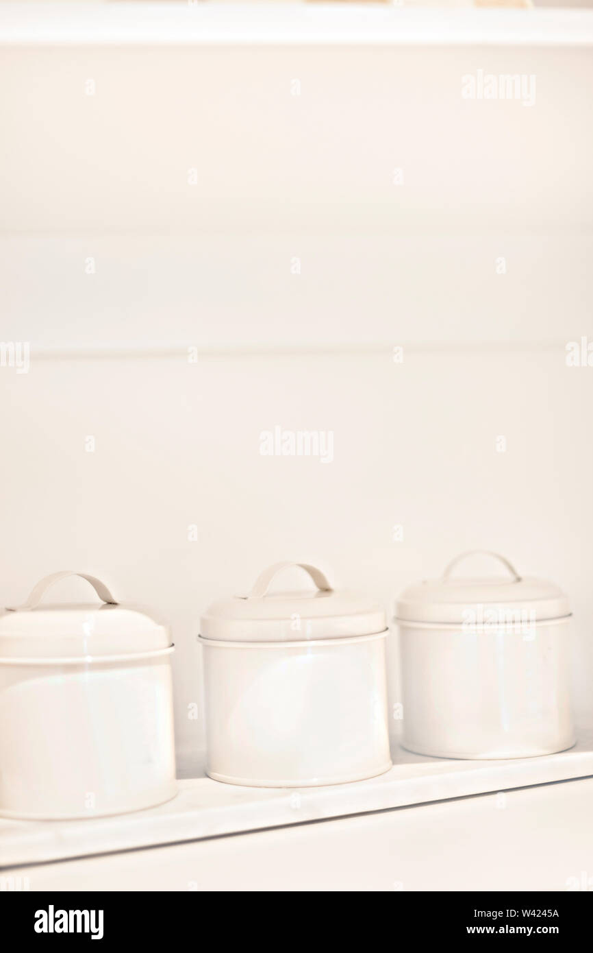 Ingredient utensils in the kitchen for making a tea in a white and wooden shelf with a space, there is three bottles. - Stock Image