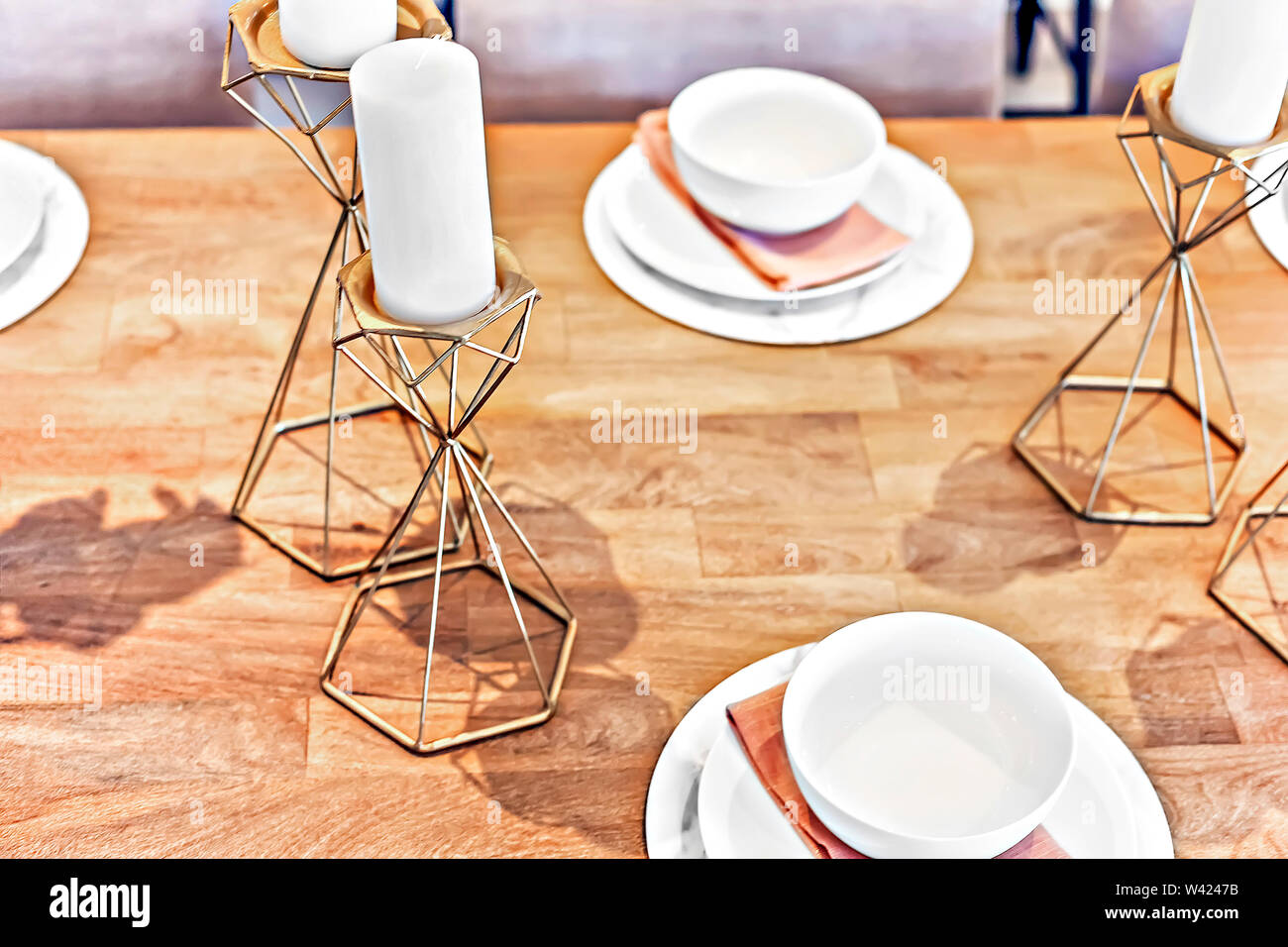Metal fancy items like gold candelabra on the table with white candles and dining table set up with dishes and mugs. the candle support is like a beve Stock Photo
