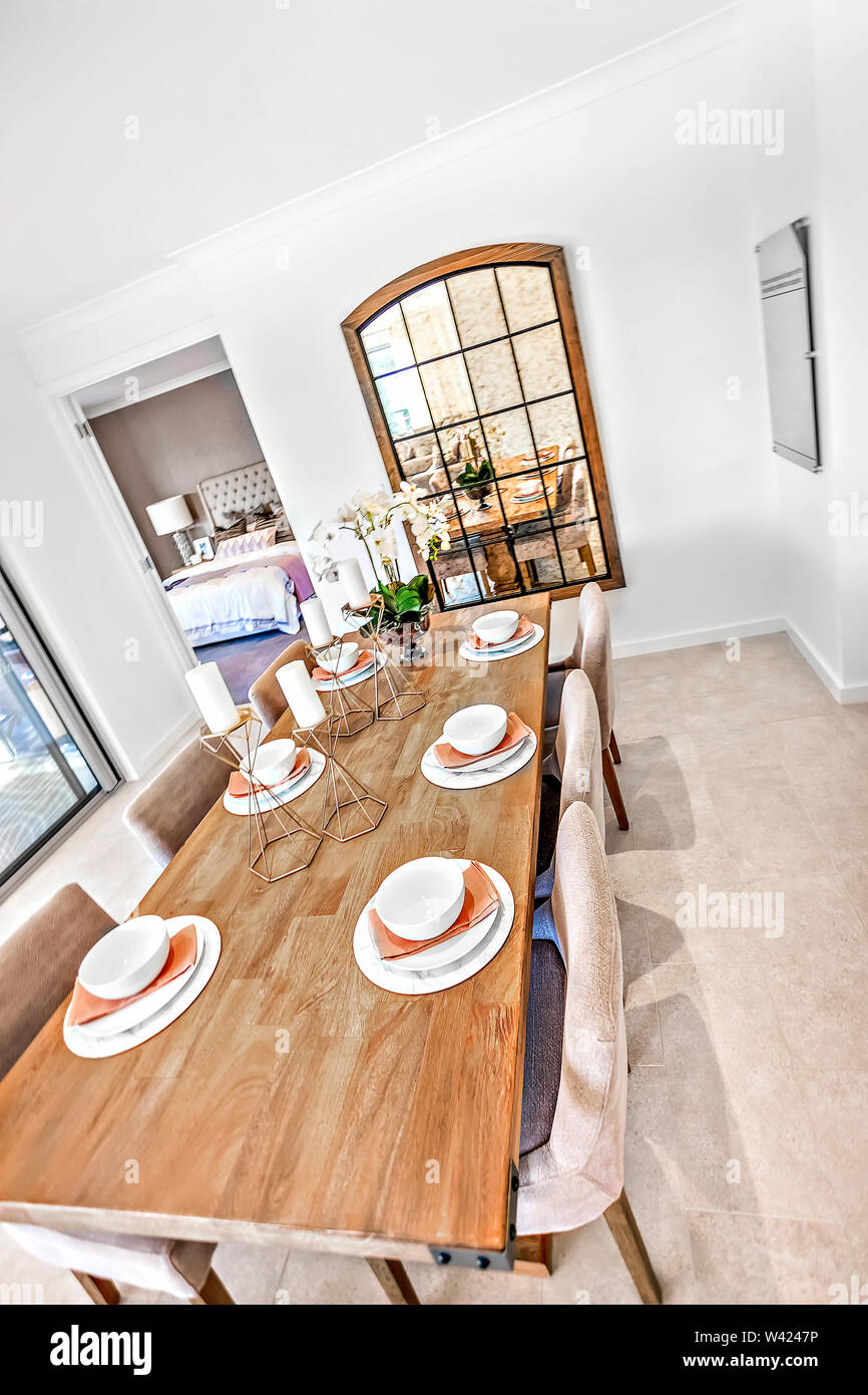 Wooden Table Set Up With Chairs And White Plates Over Napkins And Fancy Items With Chairs The Dining Room Is Included Glass Windows And Doors Stock Photo Alamy