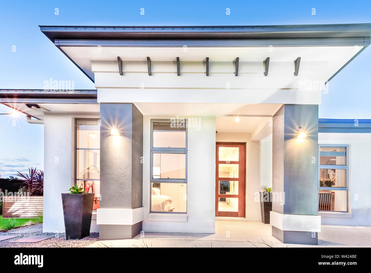 Modern House Front Close Up With Doors And Windows Beside Facade Including Big Concrete Pillars Illuminated With Lights Sky Is Clear Without Clouds Stock Photo Alamy