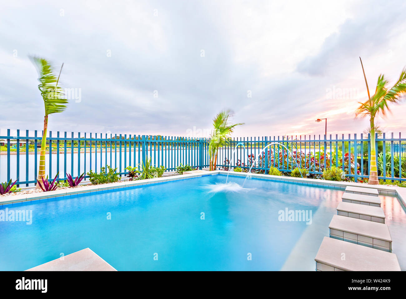 Swimming pool with blue color water and sky, garden with green trees arround the ground, sky is very attractive with sunset, evening time scene. - Stock Image