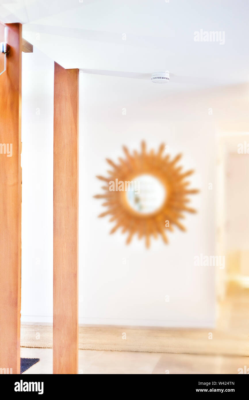 Wooden mirror on the white walls beside pillars in an area with space, the tile floor has a carpet which drives the hallway through the house, wooden - Stock Image