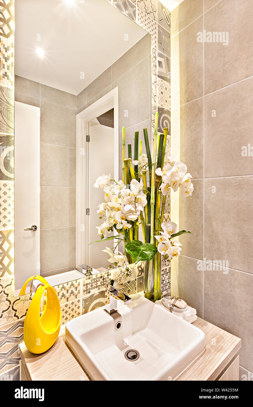 Fancy Washroom With Bamboo And White Flower Decoration Beside The Mirror With Sink And Faucet The Wall Behind The Glass Has A Various Pattern Arts Stock Photo Alamy