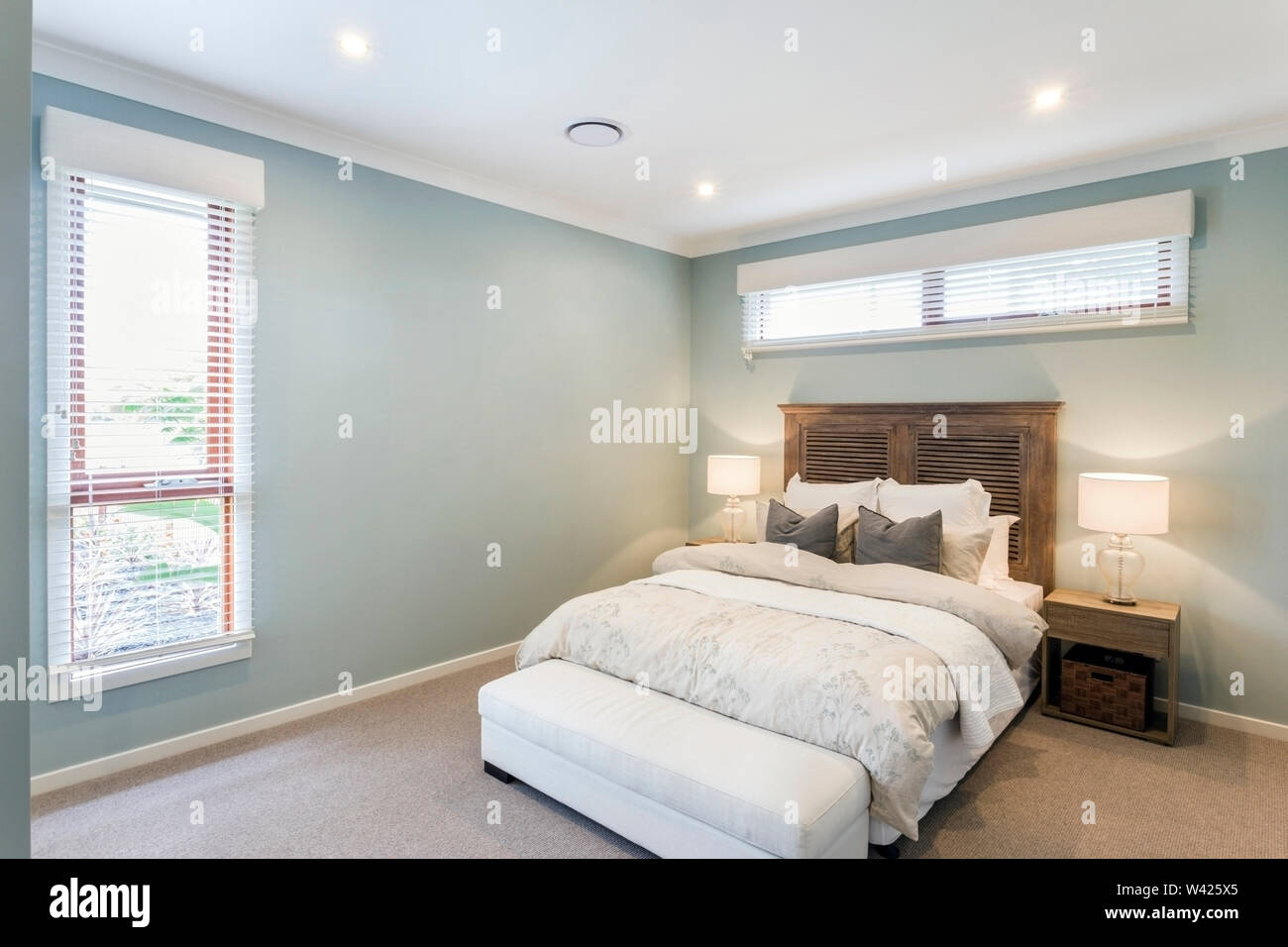 An Antique Oak Wood Finish Bed Set Paired With White Bed Covers Grey Throw Pillows And A White Bed Foot Bench Adds To The Charm Of This Classic Cont Stock Photo Alamy
