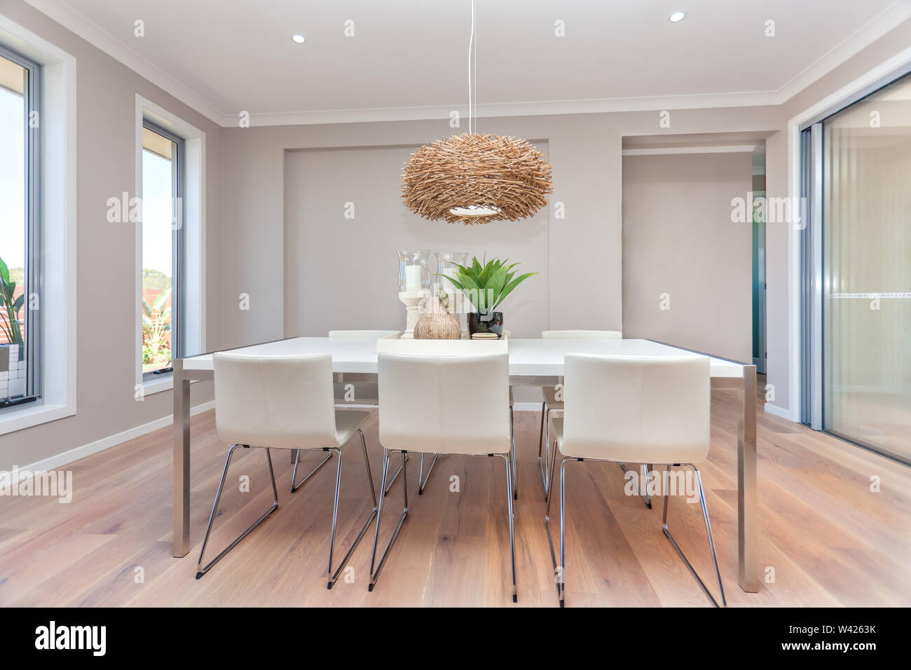 Luxury Dining Room And A Light Color Wooden Floor And Gray Walls With Two Windows Around The Area Except Right Side Glass Door And Entrance Is Next To Stock Photo Alamy