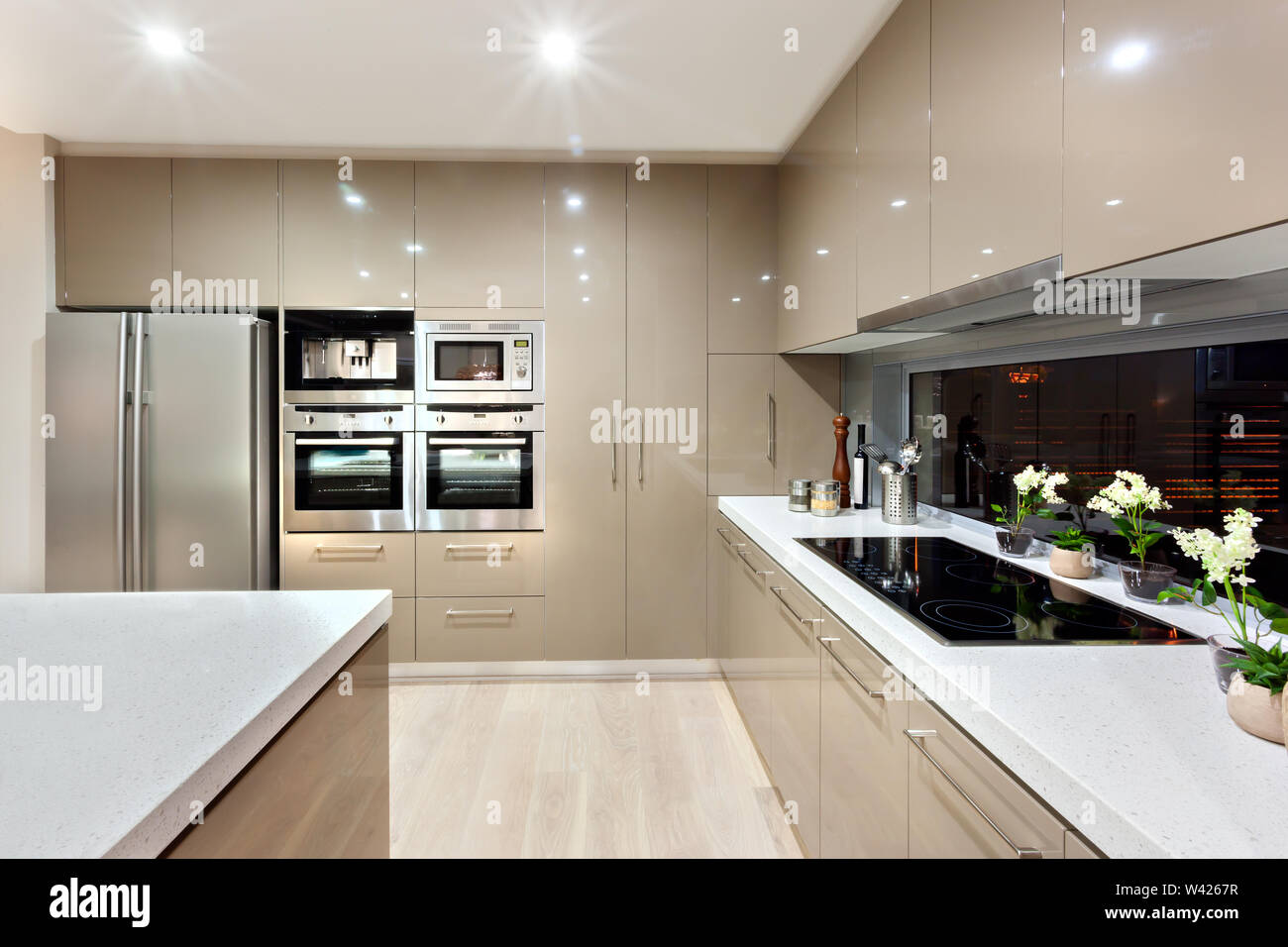 There are lots of wall cabinets and pantry cupboard fixed to the wall with A silver refrigerator and microwave oven. There are two ceramic countertops Stock Photo